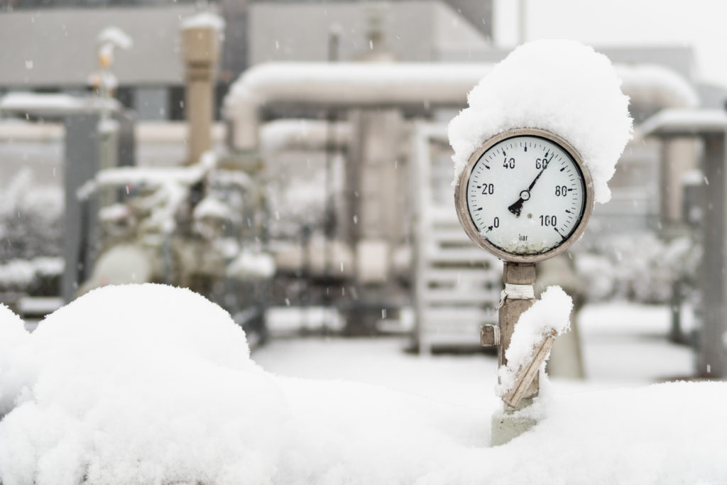 Closeup of manometer high pressure meter measuring pressure of natural gas on industrial site with valves and pipes on the background. The meter is covered with snow in cold winter. Selective focus.