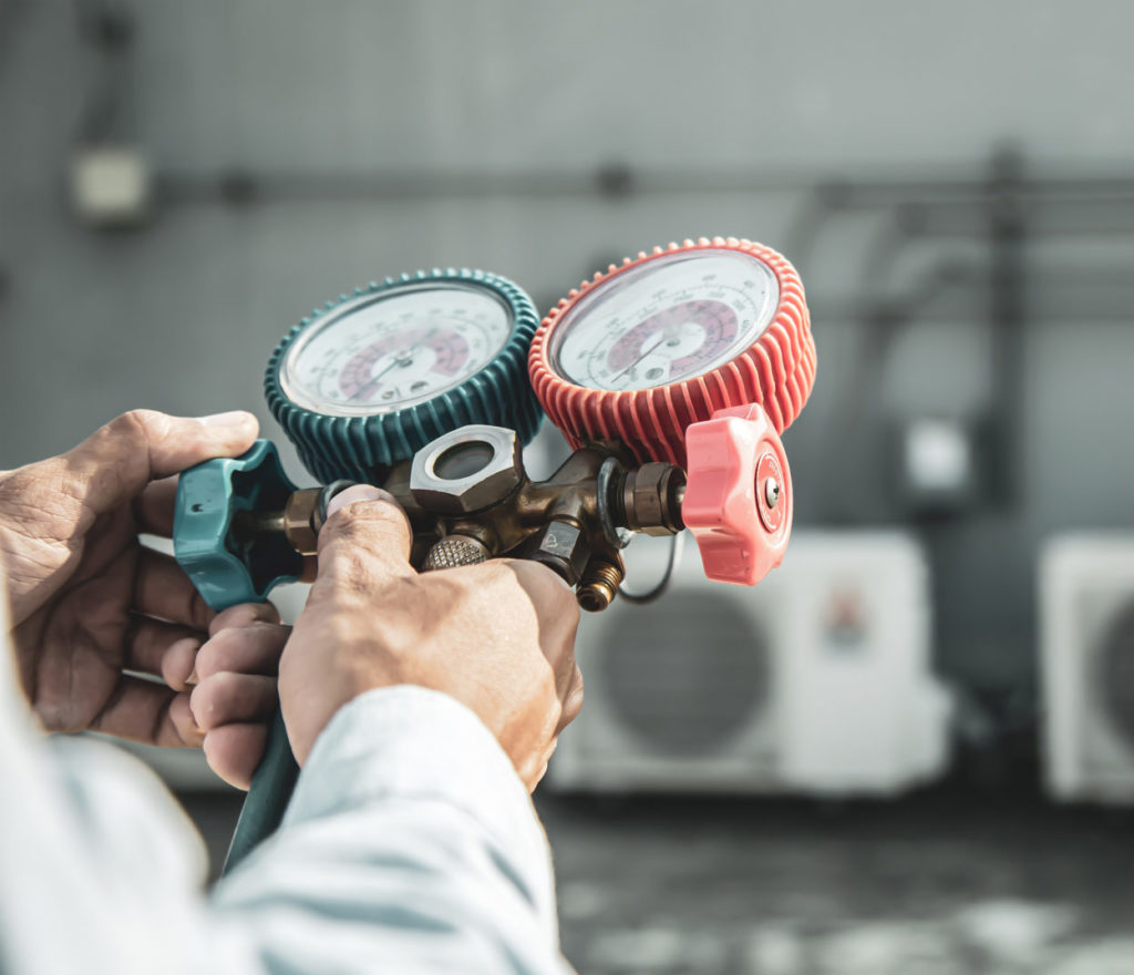 Close up hand of engineer using measuring manifold gauge for filling industrial factory air conditioners after cleaning and checking for maintenance outdoor air compressor unit.